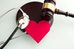 Gavel with red heart, pills, stethoscope and books on table. Medical law royalty free stock photos