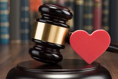 Gavel and red heart on table. Close-up Of Wooden Gavel And Red Heart On Table Royalty Free Stock Photo
