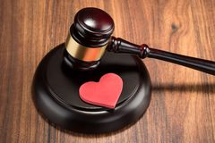 Gavel and red heart on table. Close-up Of Wooden Gavel And Red Heart On Table Stock Photography