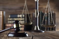Law and justice concept . Place for typography and logo. Gavel , scale of justice and legal code on wooden rustic table. Brown background Stock Photography