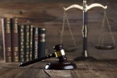 Law and justice concept . Place for typography and logo. Gavel, scale of justice and legal code on wooden rustic table. Brown background Stock Image