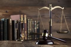 Law and justice concept . Place for typography and logo. Gavel, scale of justice and legal code on wooden rustic table. Brown background Royalty Free Stock Photography
