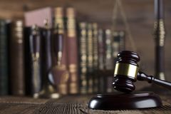 Law and justice concept . Place for typography and logo. Gavel, scale of justice and legal code on wooden rustic table. Brown background Stock Images