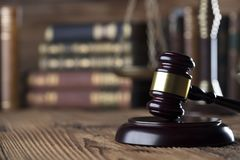 Law and justice concept . Place for typography and logo. Gavel , scale of justice and legal code on wooden rustic table. Brown background Stock Image