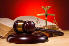 Gavel, scales of justice and old book. And red background Royalty Free Stock Photo