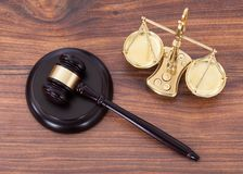 Gavel and scales with money on desk. Judge gavel and scales with money on wooden desk Royalty Free Stock Photos