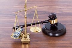 Gavel and scales with money on desk Royalty Free Stock Photography