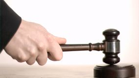 Gavel in slow motion hitting a sound block. In a bright office