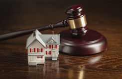 Gavel and Small Model House on Table Stock Photo