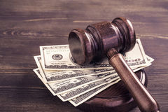 Gavel and some dollars banknotes. Auction bidding, judicial system corruption concept.Toned Stock Image