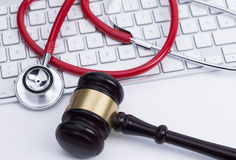 Gavel and stethoscope at the keyboard stock photo