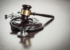 Gavel and Stethoscope on Reflective Table Stock Image