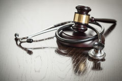 Gavel and Stethoscope on Reflective Table Stock Images