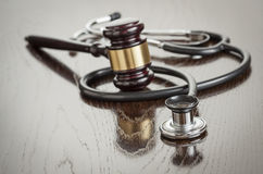 Gavel and Stethoscope on Reflective Table Stock Photography