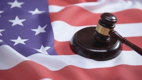 Gavel striking on sound block against american flag, case law, court system. Stock footage stock footage