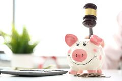 Gavel threaten to funny piggybank in time of big financial difficulties. Closeup stock photos