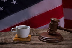 Gavel and white cup. Cup on US flag background. Morning in the courtroom. Fresh coffee for the judge royalty free stock images