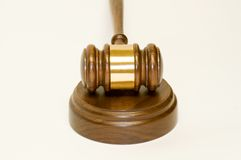 Gavel and wooden block. A wooden walnut gavel  with a brass engraving band, resting on a sounding block on a white background Stock Photos