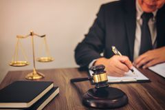Gavel on wooden table and Lawyer or Judge working with agreement Royalty Free Stock Photos