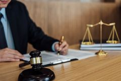 Gavel on wooden table and Lawyer or Judge working with agreement in Courtroom theme, Justice and Law concept stock image