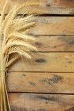 Gavilla de trigo sobre la tabla de madera Foto de archivo
