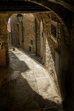 Gavorrano, Grosseto - Italy. Gavorrano province of Grosseto - Italy, medieval streets with arches and cats in the sun, stone houses and antique street lamps Royalty Free Stock Image
