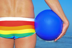 Gay beach. Someone wearing a rainbow swimsuit on the beach holding a beach ball Royalty Free Stock Photos
