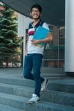 Gay bello che sta sulla via e che tiene un libro Fotografia Stock