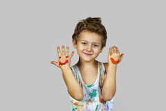 Gay boy covered in paint . Cheerful artist. A boy smeared with colours on a grey background royalty free stock image