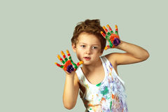 Gay boy covered in paint . Cheerful artist. A boy smeared with colours on a grey background stock image