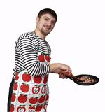 Gay cook. In apron with a frying pan in his arms Royalty Free Stock Photo