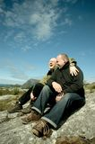 Gay couple. Sitting on rocks joking around Royalty Free Stock Photography