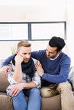 Gay couple comforting each other on the couch Stock Photo
