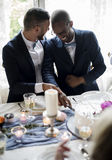 Gay Couple Cutting Cake Together on Wedding Reception. Gay couple cutting cake together on wedding party Royalty Free Stock Photos