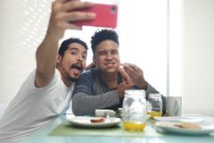 Gay Couple Eating Breakfast Taking Selfie With Phone royalty free stock image