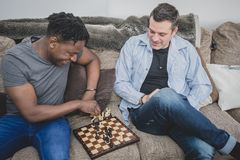 A gay couple enjoying time indoors at home, playing chess. royalty free stock image