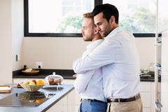 Gay couple with eyes closed hugging. At home stock image