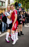 Gay couple in heels, dressed as football players. BERLIN, GERMANY - JUNE 21, 2014:Christopher Street Day.Elaborately dressed people participate in the parade Royalty Free Stock Photos