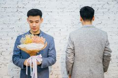 Gay couple holding a bouquet of flowers, ready to give to his partner for special occasions or wedding proposal. Asian homosexual men together Royalty Free Stock Photography
