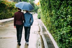 Gay couple holding umbrella and hands together. Back of homosexual men walking in the rain. Gay couple holding umbrella and hands together. Back of homosexual stock photography