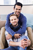 Gay couple hugging on the couch Royalty Free Stock Image