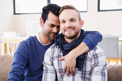 Gay couple hugging on the couch. In the living room stock photo