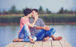 Gay couple kissing on wooden pier at riverbank Stock Image