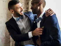 Gay Couple in Navy Blue Tuxedo Sitting Together royalty free stock photography