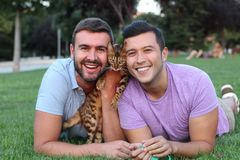 Gay couple in the park with their pet.  royalty free stock photos