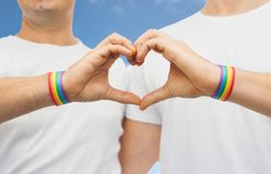 Gay couple with rainbow wristbands and hand heart Royalty Free Stock Photography