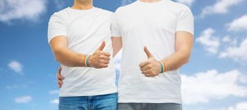 Gay couple with rainbow wristbands shows thumbs up Royalty Free Stock Images