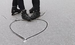 Gay couple skating drew a heart in the snow. royalty free stock photo