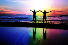 Gay couple at sunset. Silhouette of a gay couple on the beach with a rainbow sunset Stock Image