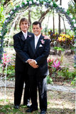 Gay Couple Under Wedding Arch. Newly married gay couple posing for a portrait under the wedding arch Royalty Free Stock Images